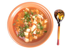 Placa de la sopa de verduras y una cuchara de madera aislada en el CCB blanco Imagen de archivo libre de regalías