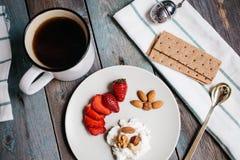 Placa de la visión superior A con requesón, fresas y nueces, una taza de café y toallas en una tabla de madera imágenes de archivo libres de regalías