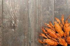 Placa de lagostas vermelhas na tabela de madeira velha no canto da esquerdo-parte inferior Imagens de Stock Royalty Free
