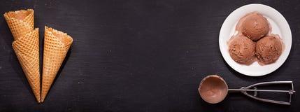 Placa de las cucharadas del helado de chocolate y de los conos de la galleta fotografía de archivo libre de regalías
