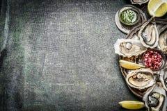 Placa de las ostras del aperitivo con el limón y las salsas en fondo rústico Fotografía de archivo