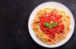 Placa de las pastas con la salsa de tomate y la albahaca verde imagenes de archivo