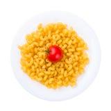 Placa de las pastas crudas con el tomate aislado en blanco Foto de archivo libre de regalías