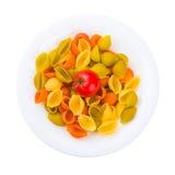 Placa de las pastas crudas con el tomate aislado en blanco Foto de archivo