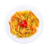 Placa de las pastas crudas con el tomate aislado en blanco Imagen de archivo