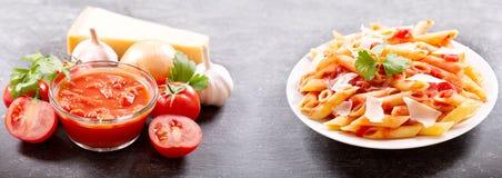 Placa de las pastas del penne con la salsa y el parmesano de tomate imagenes de archivo