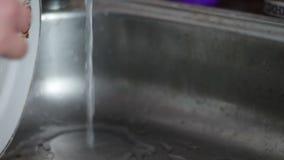 Placa de lavagem da mulher na banca da cozinha vídeos de arquivo