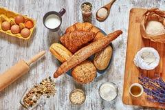 Placa de los ingredientes del pan fresco y de la hornada en una tabla de madera Foto de archivo