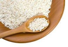 Placa de madeira com grões do arroz imagem de stock