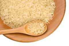 Placa de madeira com grões do arroz foto de stock royalty free