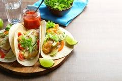 Placa de madeira com os tacos de peixes saborosos Imagem de Stock