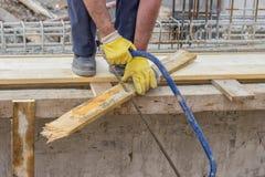 A placa de madeira do sawing do trabalhador de Bulder com mão considerou Imagens de Stock
