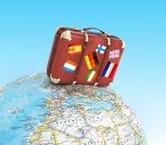 Placa de madeira do sinal e mala de viagem velha com as bandeiras dos striples no mapa do mundo borrado Imagem de Stock