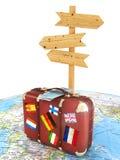 Placa de madeira do sinal e mala de viagem velha com as bandeiras dos striples no mapa do mundo borrado Fotografia de Stock
