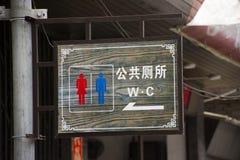 A placa de madeira ou a etiqueta de madeira para o guia direto v?o ao toalete p?blico na passagem ao lado da estrada em exterior  fotografia de stock royalty free
