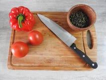 Placa de madeira para cortar alimentos na tabela na cozinha fotografia de stock