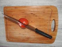 Placa de madeira para cortar alimentos na tabela na cozinha fotografia de stock royalty free