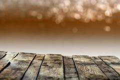Placa de madeira resistida velha ou tampo da mesa rústico com um bokeh efervescente de luzes douradas do partido no fundo imagem de stock royalty free