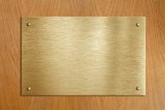 Placa de madera con oro o la placa de cobre amarillo Fotografía de archivo libre de regalías