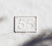 Placa de metal pintada con la pintura de la pared que muestra el número 55 Imágenes de archivo libres de regalías