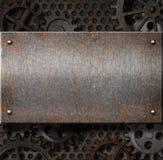 Placa de metal sobre o fundo oxidado das engrenagens Fotografia de Stock