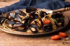 placa de oro del metal con espaguetis deliciosos y mejillones italianos tradicionales cocinados en salsa con los tomates fotos de archivo libres de regalías