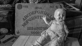 Placa de Ouija e boneca assustador fotografia de stock