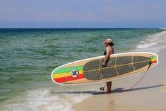 Placa de pá triplicar-se X da terra arrendada do surfista na praia foto de stock royalty free