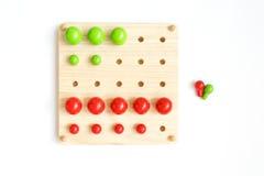 Placa de Pegs colorida, grânulos de madeira no fundo branco Foto de Stock
