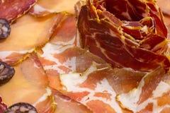 Placa de presuntos cortados diferentes O choron cru espanhol e o chouriço vermelho arranjaram em uma flor fotografia de stock