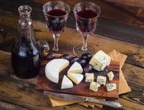 Placa de queijo com uva e vinho na madeira Imagem de Stock Royalty Free