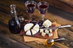 Placa de queijo com uva e vinho na madeira Imagens de Stock