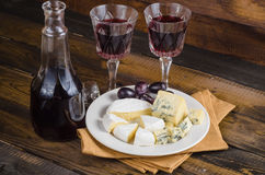 Placa de queijo com uva e vinho na madeira Imagem de Stock