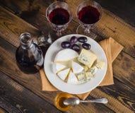 Placa de queijo com uva e vinho na madeira Imagens de Stock Royalty Free