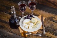 Placa de queijo com uva e vinho na madeira Foto de Stock