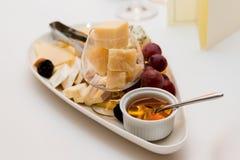 Placa de queijo com uvas e mel Fotos de Stock Royalty Free