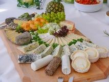 Placa de queijo com variedade de aperitivos na tabela um de madeira Fotografia de Stock Royalty Free