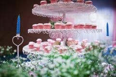 Placa de queques coloridos deliciosos em uma placa branca no casamento Imagem de Stock