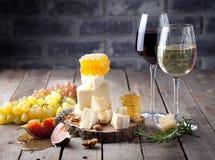 Placa de queso con la miel, uva, vino en vidrios Fotos de archivo libres de regalías