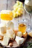 Placa de queso con la miel, uva, vino en vidrios Fotografía de archivo