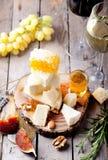 Placa de queso con la miel, uva, vino en vidrios Imagen de archivo libre de regalías