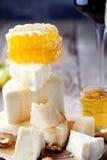 Placa de queso con la miel, uva, vino en vidrios Imagenes de archivo