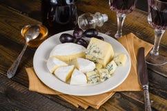 Placa de queso con la uva y el vino en la madera Fotografía de archivo