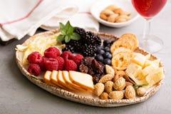 Placa de queso con las nueces y las bayas Imagenes de archivo