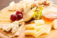 Placa de queso con las uvas Imágenes de archivo libres de regalías