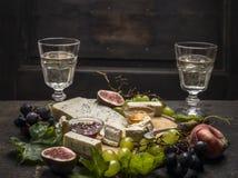 Placa de queso con las uvas blancas y oscuras sobre los vidrios de los melocotones de una rama en fondo rústico de madera Imagen de archivo