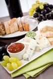Placa de queso con las uvas y la cena del vino Imagen de archivo