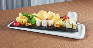 Placa de queso deliciosa en una tabla del restaurante Foto de archivo