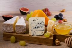 Placa de queso Diversos tipos de queso con las uvas, la miel, los higos y las nueces en la tabla de madera rústica imagen de archivo