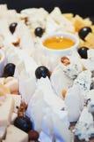 Placa de queso El surtido de queso con las nueces y la miel del cazo de la miel en la porción de madera blanca suben sobre el tex Fotografía de archivo